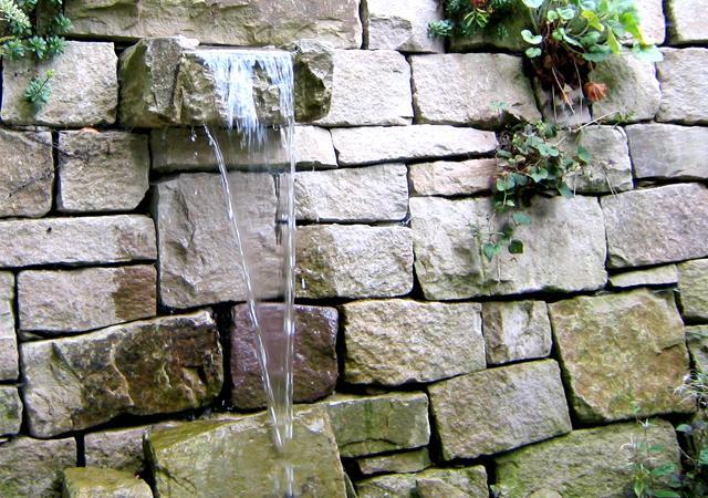Natursteinmauer mit kleinem Wasserspeier.