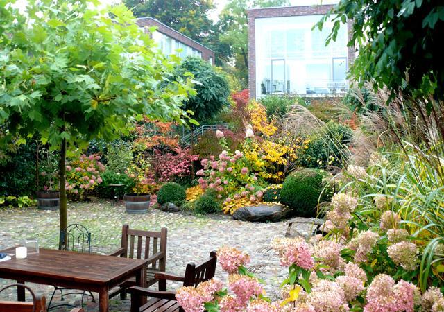 Die Mitte des Gartens bildet eine gepflasterte Fläche.