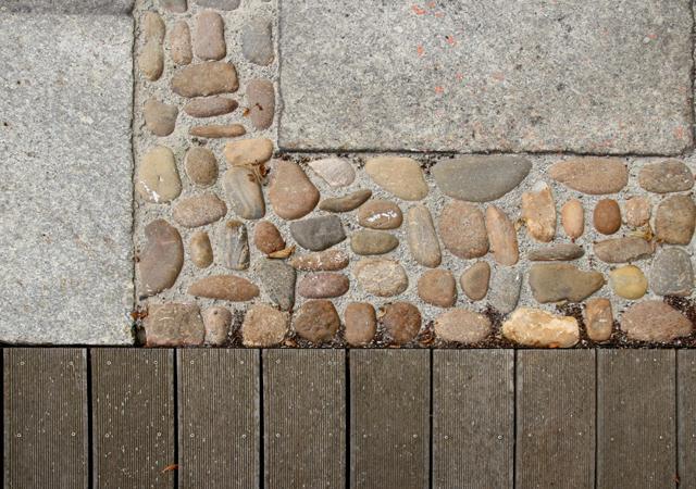 Holzdeck, Katzenkopfpflaster und Großsteinplatten.