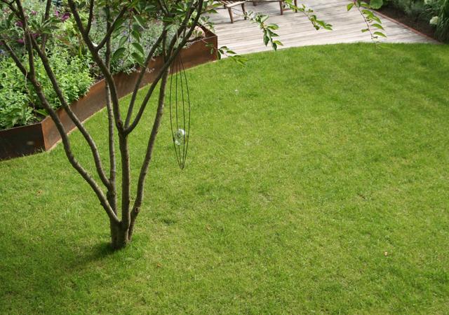 Rasenrund und Hochbeet aus rostbraunem Stahl.