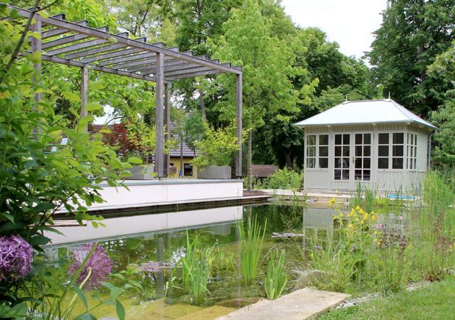 Eine moderne Pergola begleitet das Holzdeck am Schwimmteich.
